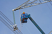 Electrical workers high above the ground building a high voltage utility tower.