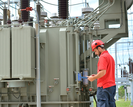 Engineer with red hardhat and protective workwear at work in power plant, near transformer.