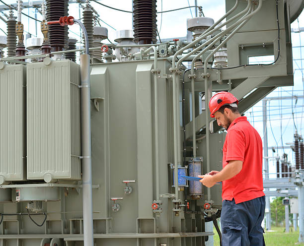 Electrician and High Voltage Transformer Engineer with red hardhat and protective workwear at work in power plant, near transformer. electricity transformer stock pictures, royalty-free photos & images