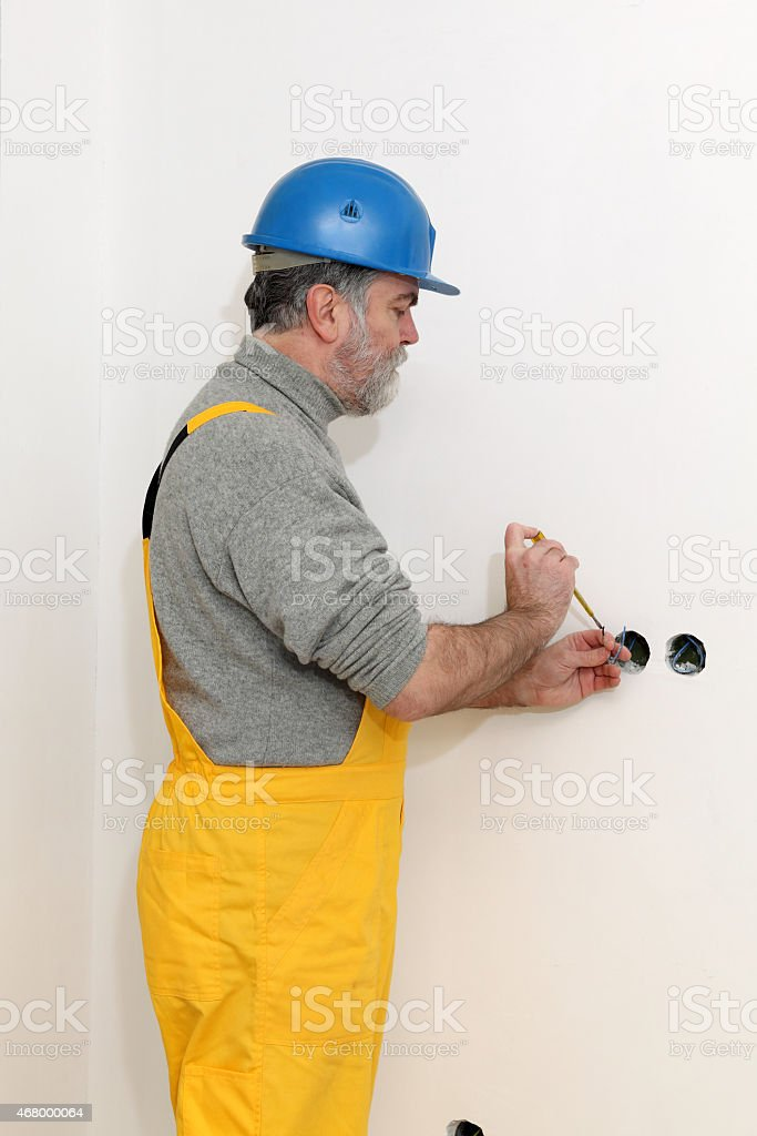 Electrician at construction site testing installation stock photo