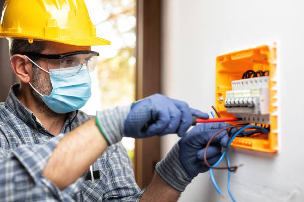 elektryk w pracy z twarzą chroniona maską chirurgiczną, aby zapobiec zakażeniu coronavirus. pandemia covid-19. - przewód składnik elektryczny zdjęcia i obrazy z banku zdjęć