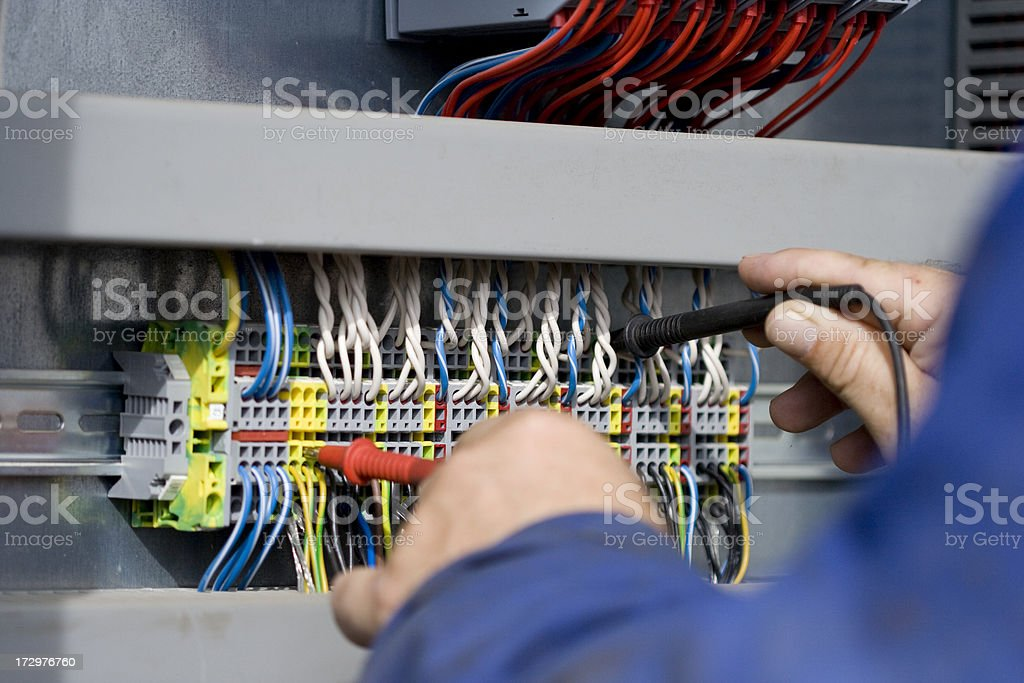 Electrician at work with his instrument of measurement. stock photo