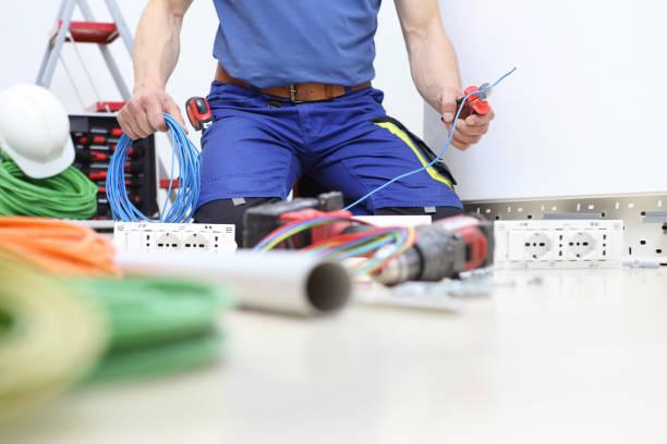 elektricien op het werk met nippers in de hand knippen van de elektrische kabel, installatie van elektrische circuits, elektrische bedrading - elektrische fitting stockfoto's en -beelden