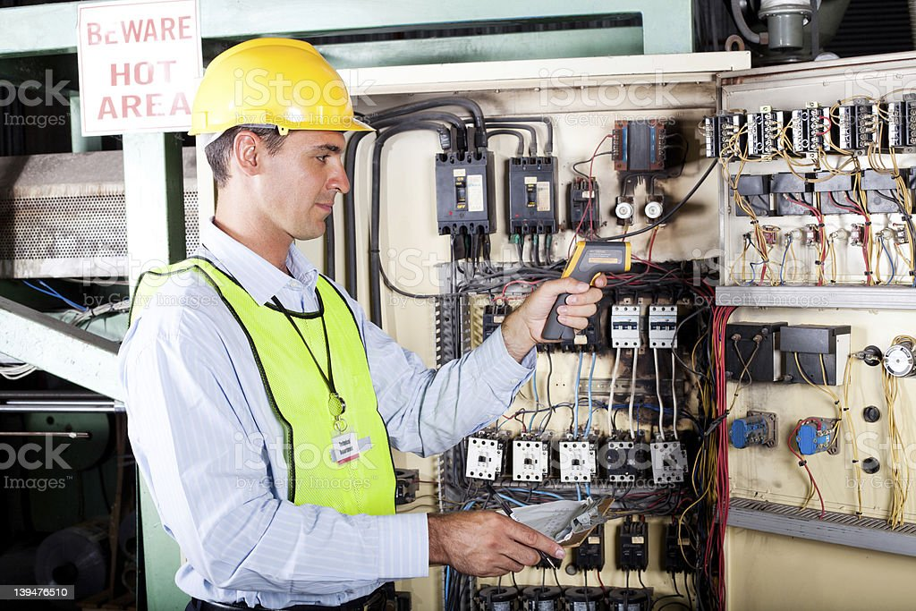 electrician checking industrial machine control box temperature royalty-free stock photo