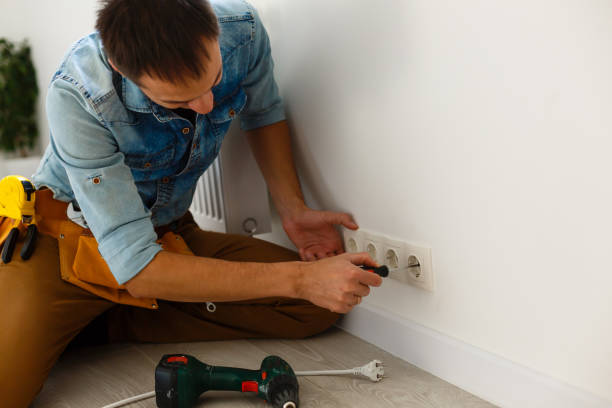 Electrician checking socket voltage with digital multimeter stock photo