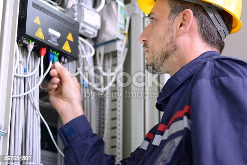 Engineer inspecting cabling connection in electrical room.