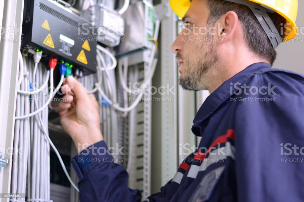 Electrician connecting cable to the switch stock photo