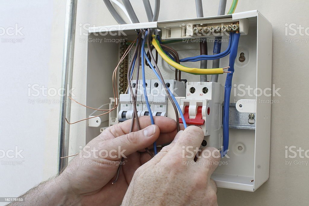Electrician connecting up a fuse box. royalty-free stock photo