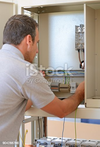 istock Electrician connecting wires in the electrical cabinet in power station 904288786