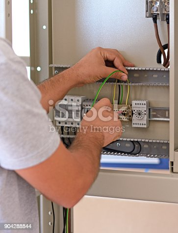 istock Electrician connecting wires in the electrical cabinet in power station 904288844