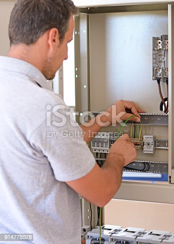 istock Electrician connecting wires in the electrical cabinet in power station 914775078