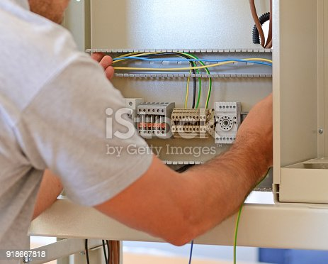 istock Electrician connecting wires in the electrical cabinet in power station 918667818