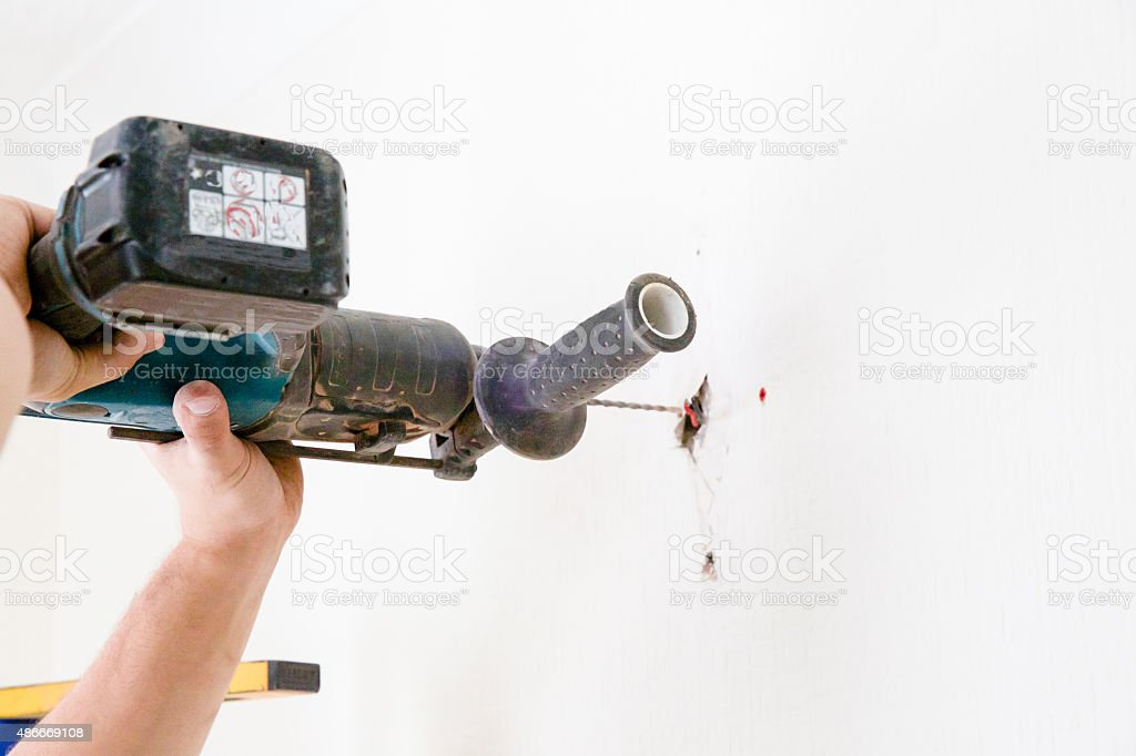 Electrician drilling the wall for wall lights stock photo