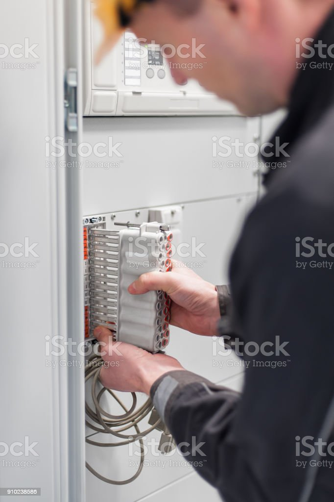 Electrician engineer tests electrical installations on relay protection system stock photo