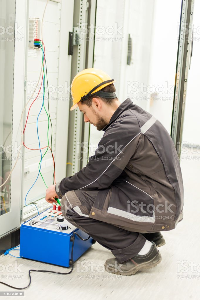 Electrician engineer tests system with relay test set equipment stock photo