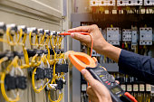 istock Electrician engineer work  tester measuring  voltage and current of power electric line in electical cabinet control. 1150199542