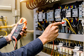 istock Electrician engineer work  tester measuring  voltage and current of power electric line in electical cabinet control. 1150199564