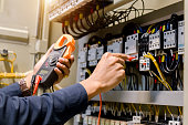 istock Electrician engineer work  tester measuring  voltage and current of power electric line in electical cabinet control. 1150199580