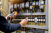 istock Electrician engineer work  tester measuring  voltage and current of power electric line in electical cabinet control. 1150199677