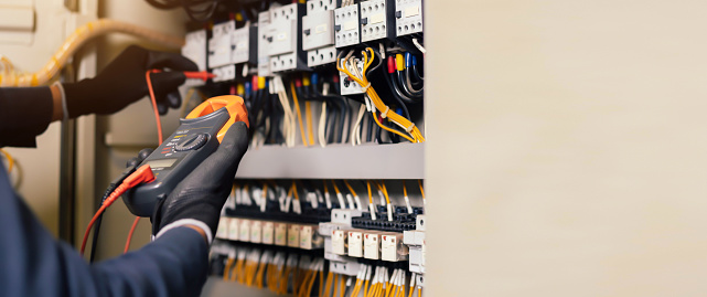 Electrician engineer work tester measuring voltage and current of power electric line in electical cabinet control.and wires on relay protection system. Bay control unit. Medium voltage switchgear.