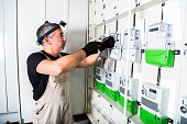 Electrician engineer works with screwdriver on fuse switch box
