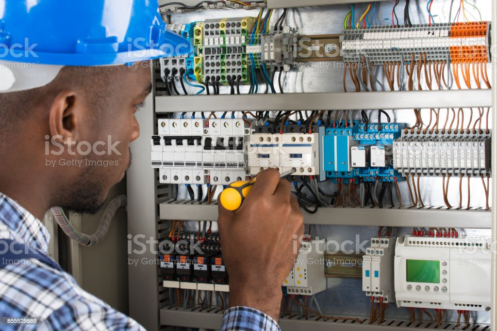 Electrician Examining Fusebox With Screwdriver stock photo