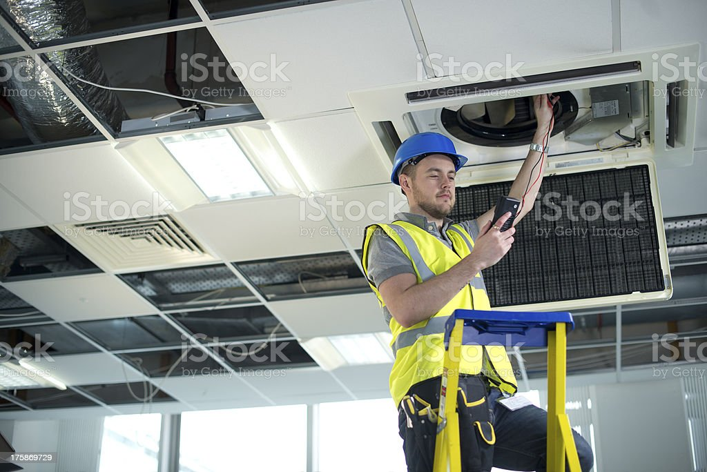 electrician fitting air conditioning to office interior stock photo