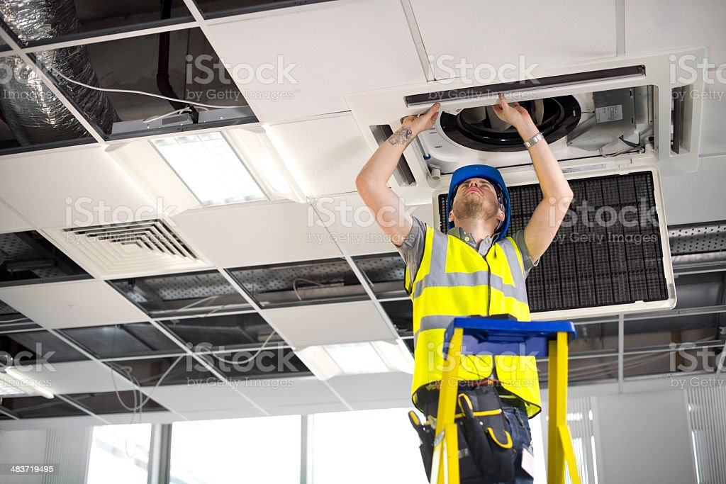 electrician fitting air conditioning to office interior royalty-free stock photo