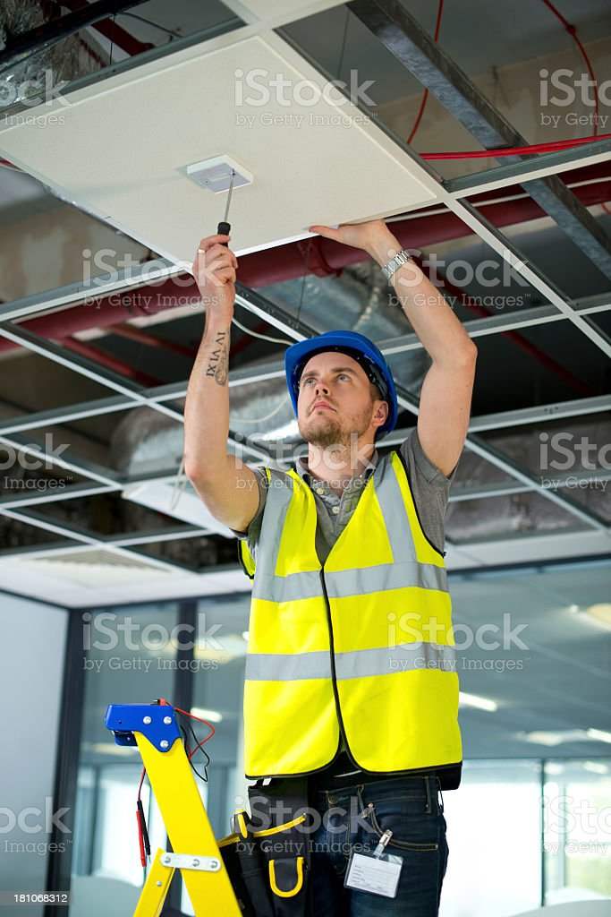 electrician fitting sensor to office interior stock photo