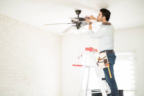 Electrician fixing a ceiling fan Profile view of a male electrician stepping on a ladder and installing a ceiling fan in a house ceiling fan stock pictures, royalty-free photos & images