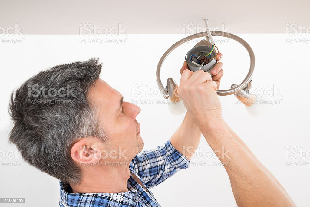 Electrician Fixing Light On Ceiling stock photo