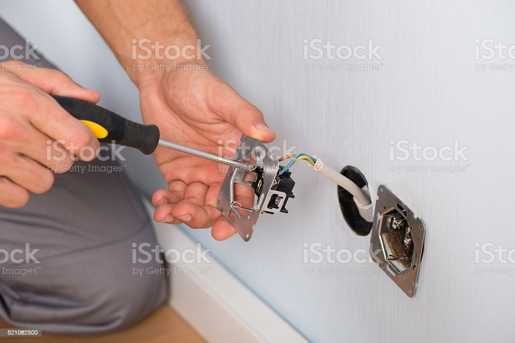 Electrician Hands Installing Wall Socket stock photo