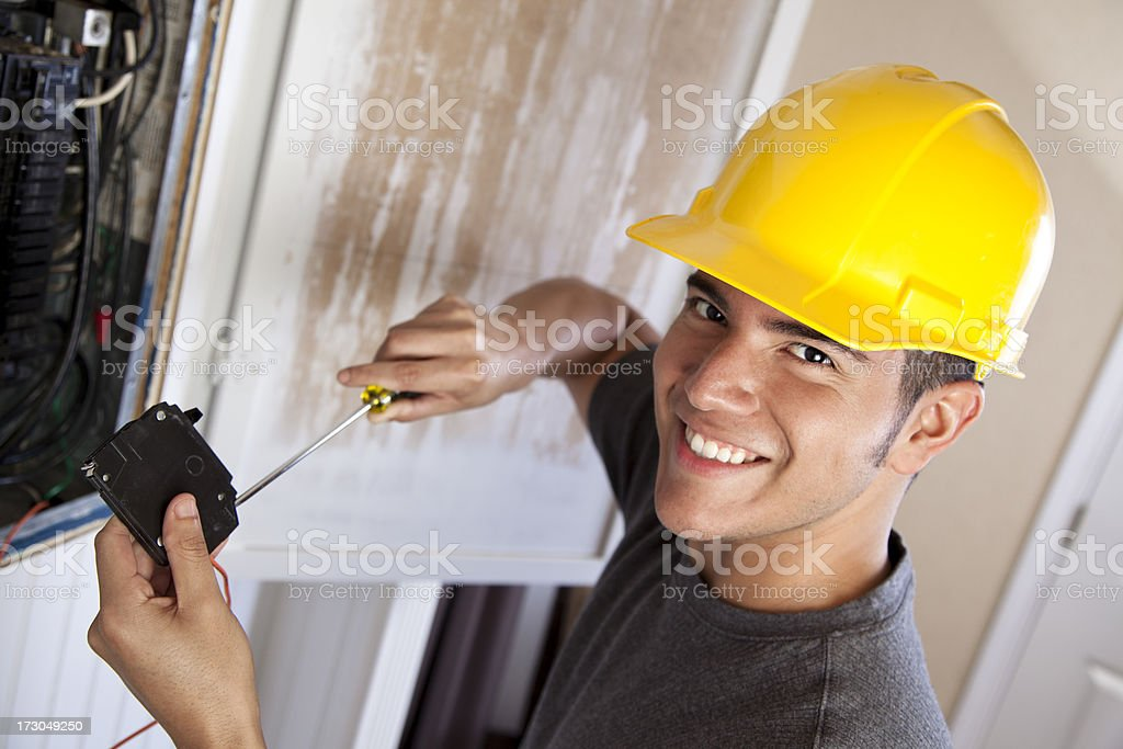 Electrician in hard hat working on circuit breaker stock photo