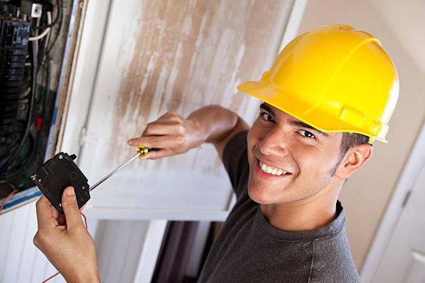 Electrician in hard hat working on circuit breaker stock photo