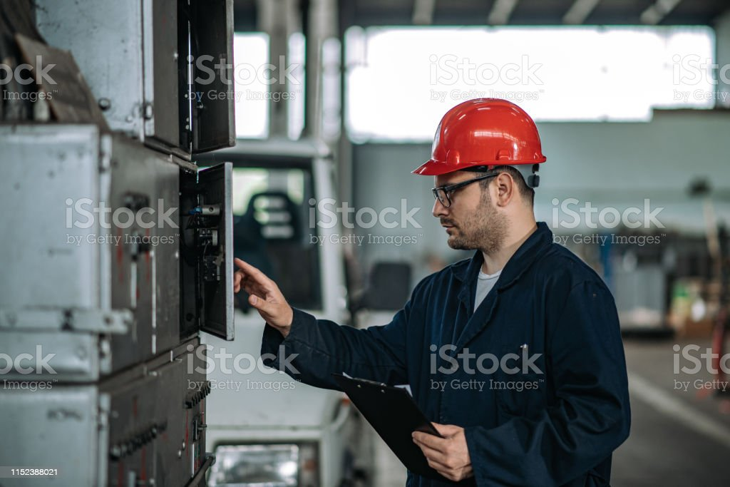Electrician in protective work wear at work in factory hall.