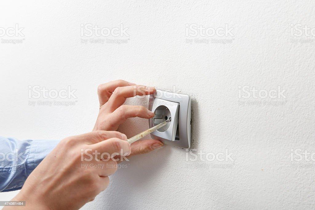 Electrician installing AC power socket stock photo