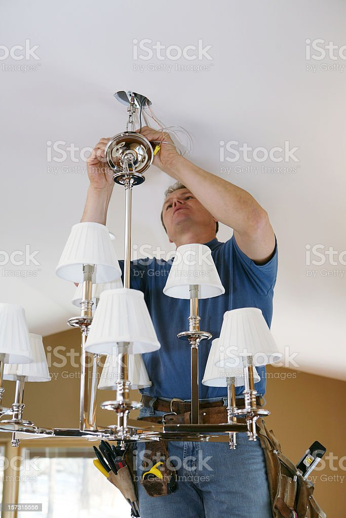 Electrician Installing Designer Chandelier stock photo