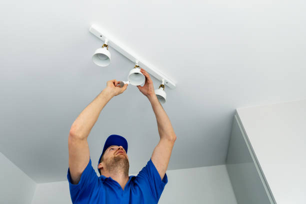 electrician installing led light bulbs in ceiling lamp stock photo