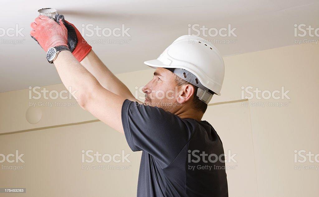 Electrician installing light bulb stock photo