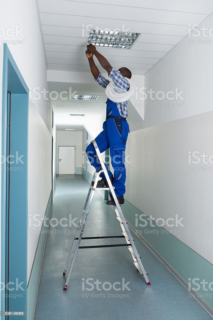 Electrician Installing Light On Ceiling stock photo