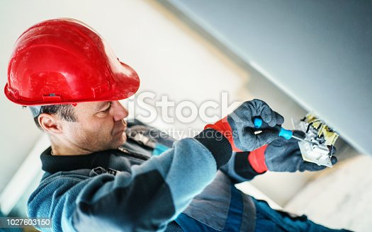 Closeup side view of an electrician connecting wires during process of installing light switch. He's wearing red protective gloves and work helmet.