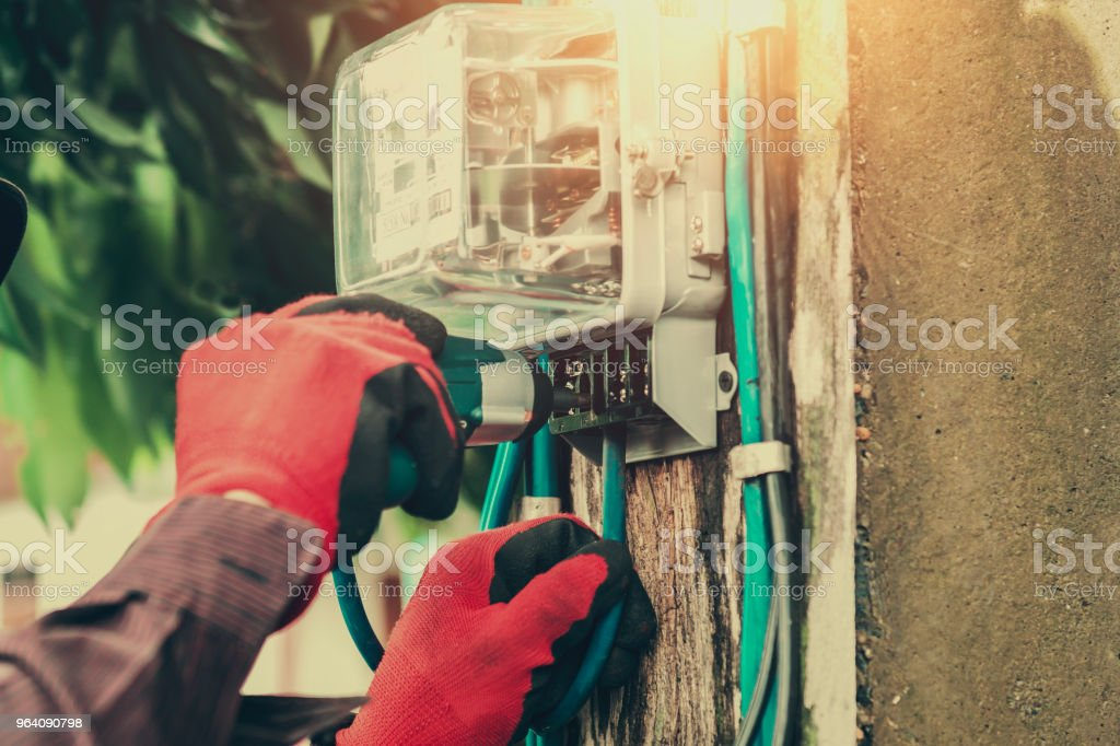 electrician installing watthour meter at home - Royalty-free Adult Stock Photo