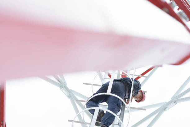 Electrician is climbing on cell tower, working at height stock photo