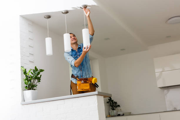 Electrician is installing and connecting a lamp to a ceiling. stock photo