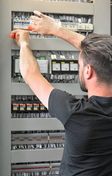 Electrician is Repairing Electrical Failure on the Fuse Box stock photo