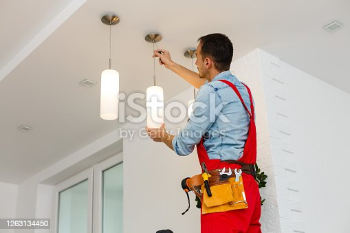 Electrician man worker installing ceiling lamp