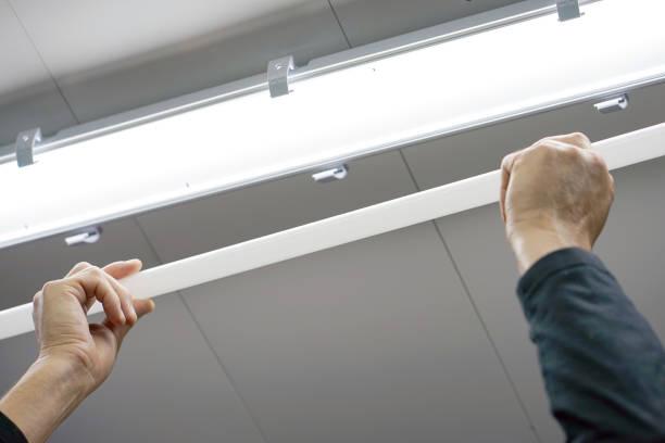 elektriker mann arbeiter installation leuchtstofflampe - fluoreszierend stock-fotos und bilder