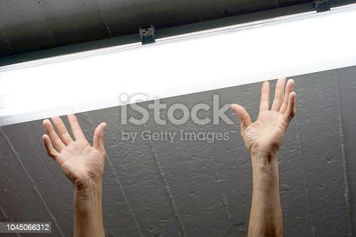 istock Electrician man worker installing fluorescent lamp 1045066312