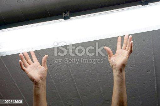 istock Electrician man worker installing fluorescent lamp 1070743508