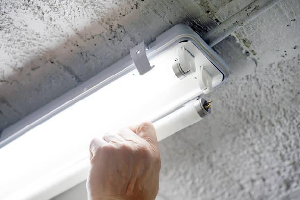 elektroarbeiter installiert leuchtstofflampe - glühbirne auswechseln stock-fotos und bilder
